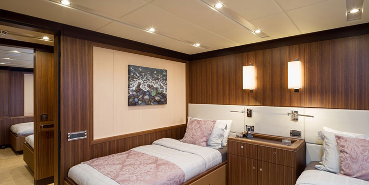 Two guest staterooms, both aft, are among the accommodations aboard this sloop. Rhoades Young Design worked with Yin to create a simple, linear decor, highlighted by French walnut paneling and white oak soles. Photo by Carlo Baronicini.