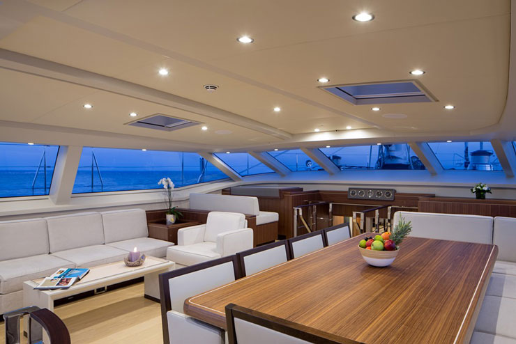An intimate conversation area and a dining area comprise the immediate interior of the deckhouse. Forward to port there's also an extra helm, handy in case of particularly inclement weather. Photo by Carlo Baronicini.