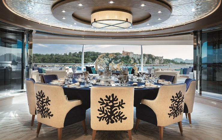 The owners excluded a formal dining area from the main deck, wanting it up one level and aft instead. Varying shades of blue, including in hand-painted murals, define the décor. So, too, does the wave pattern underfoot, echoed in carved oak panels in other rooms.