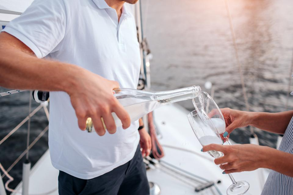 Man pouring champagne into glasses on a yacht. Woman holds them. They stands at bow of white yacht.
